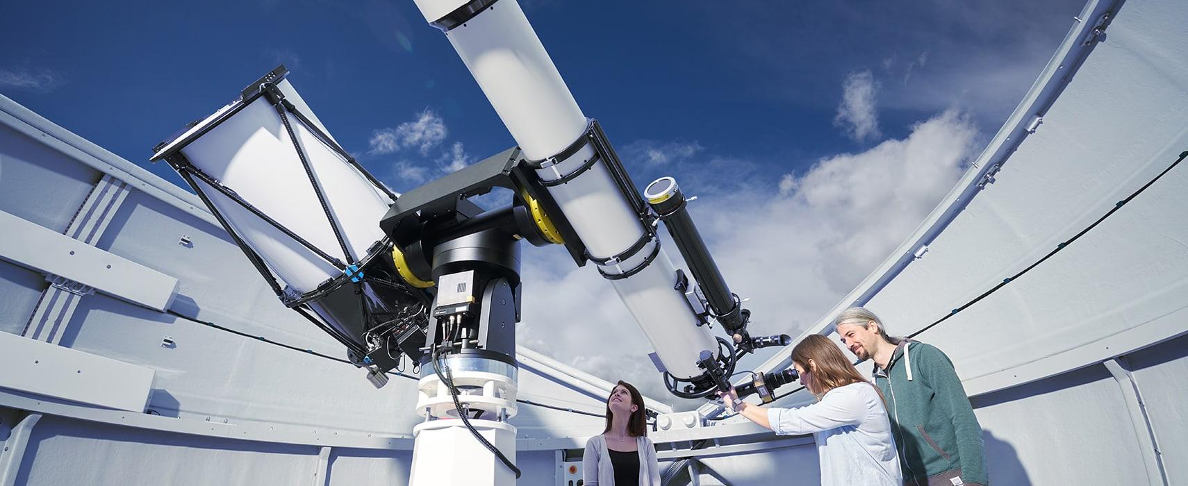 Personen sehen durch das Teleskop auf Sterne und ferne Galaxien